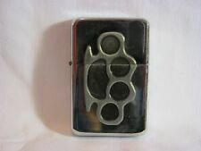 Flint lighter.  Silver with brass knuckles design.