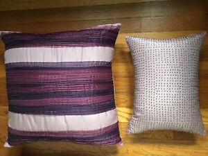 A pair of different matching purple pillows for a bed