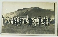Real Photo Band Musicians at Foot of Mountains Buildings RPPC Postcard H14