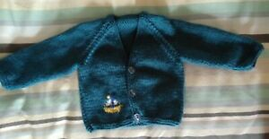 Hand-knitted newborn size v-neck baby cardigan in teal, with boat motif.