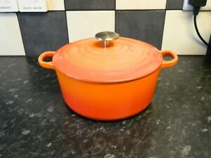 cast iron casserole dish and lid in orange size 22