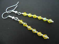 A PAIR OF YELLOW  CRYSTAL  SILVER PLATED DANGLY EARRINGS.