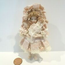 MINIATURE LITTLE GIRL DOLL DRESSED IN PINK HOLDING HER DOLL