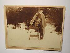 im Garten stehender Junge in Mantel & Mütze - Hund Stuhl Winter / kleines KAB
