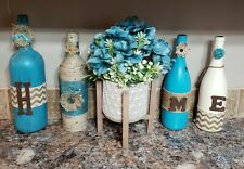 Decorative wine bottles. Blue with floral arrangement.