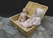 TWO ALL BISQUE BABY DOLLS WITH WICKER BED