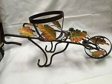 wrought iron wheelbarrow with a glass bowl can be uesdf for a floral arragement