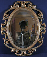 Antique carved gilded frame with an oval mirror