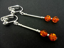 A PAIR OF SILVER PLATED AMBER GLASS BEAD CLIP ON DANGLY EARRINGS. NEW.