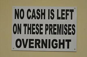 White plastic shop sign printed black no cash left on premises HOLED, DRILLED