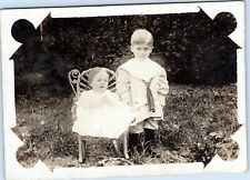 rppc Stern faced young boy with toddler in chair outside - by D. W. Clotfelter