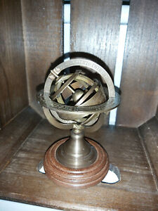 A BRASS ARMILLARY SPHERE ON A WOODEN STAND FROM INDIA