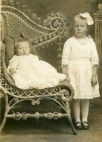 RPPC ADORABLE CHILDREN GIRL w HAIR BOW BABY RATTAN SETTEE REAL PHOTO POSTCARD