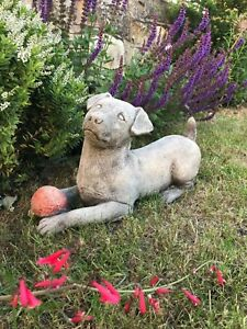 Jack russell puppy dog with red ball stone garden ornament, cute dog play laying