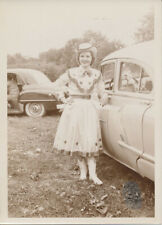 PORTRAIT OF BEAUTIFUL SMILING COWGIRL POSING W/ VINTAGE CARS