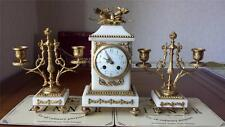 An early 20th C French gilt metal & marble clock with a pair of candlesticks