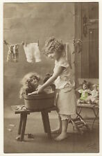 ADORABLE GOLDEN HAIRED LITTLE GIRL GIVES HER DOLLS A BATH (REAL PHOTO POSTCARD)