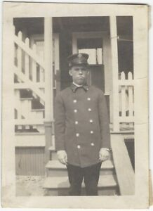 Grumpy Young Fireman in Uniform Poses by Wooden Stairs Vintage Snapshot