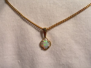 Lot 696  10k Gold Crystal Opal Pendant, showing green colour and simple setting.