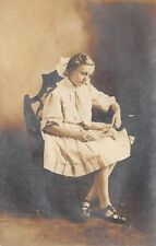 1910s RPPC Real Photo Postcard Girl in Chair Fancy Dress Bow Looks At Photograph