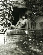 Beautiful young nude woman curly hair sitting in window snapshot vintage