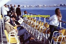 1977 35mm Slide/Tourists On Boat/City Background/Ocean/Man Reading Paper SL247