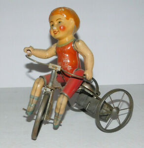 VINTAGE PREWAR TIN & COMPOSTION BOY OF WIND-UP TOY TRICYCLE WITH STEEL WHEELS