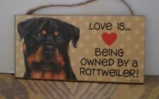 WOOD SIGN OF LOVE IS BEING OWNED BY A ROTTWEILER