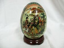 Asian painted scene on ceramic egg with wood pedestal