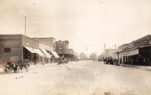 H65/ Holly Colorado RPPC Postcard c1920 Main Street Stores Automobiles 65