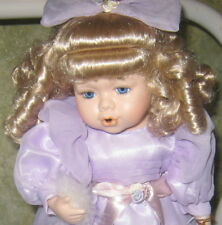 BEAUTIFUL PORCELAIN DOLL WITH BLOND HAIR AND PURPLE DRESS BLOWING A FUR BALL
