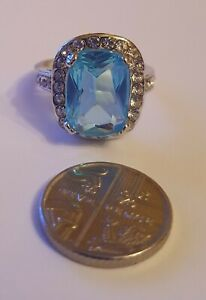 Simulated Swiss Blue and Simulated Diamond Halo Ring in Silver Plated. Size P.