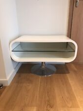 White oval TV stand with clear glass storage shelf