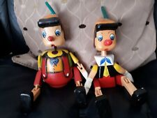 Two Pinocchio wooden hand made jointed & painted dolls 11 & 8 inches long.