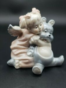 Child hugging Teddy Bear Figurine marked CB.  Muted pink & blue colors