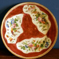 An antique plate with hand painted flowers and red trefoil