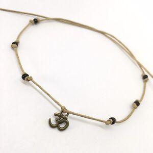 Beige string bronze OM AUM tie-on bracelet with black glass beads karmastring UK