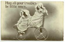 1910 pair of puppy dogs dressed as babies in a baby carriage