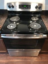 Brand new stainless steel and black stove with over head fan