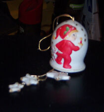 Hanging bell decorated with a child wearing red sleeper pj's and a red and whit