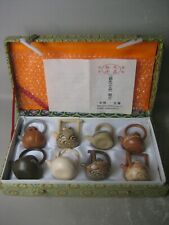 Set of 8 Oriental miniature purple sand teapots and original box, collectable