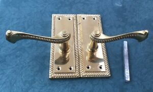 A pair of antique style roped cast brass lever door handles with spindle