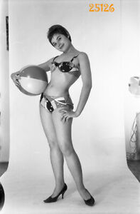 short haired girl in  home made studio, stiletto shoes, 1970s vintage negative