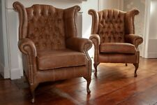 A pair of Queen Anne wing back chairs and footstool in vintage tan leather