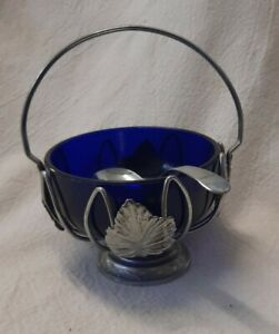 vintage metal basket with blue glass insert and spoon.