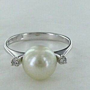 AN ANTIQUE  EIGHTEEN CARAT WHITE GOLD,PEARL AND  SMALL DIAMOND RING.