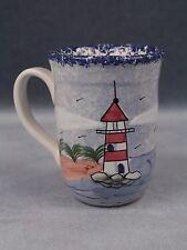 Lighthouse Coffee Mug, w/ white light beams, blue ocean, beach shore, green tree