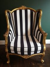 Antique newly upholstered black and white stripe wingback chair with aged gold f