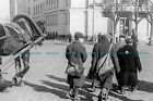 F000918 Jewish people walk alongside a horse drawn carriage on a road in the Rig