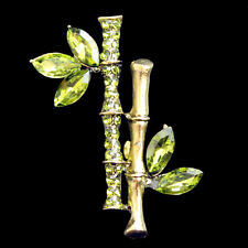Brosche Bambus Zweig mit grünen Kristallen antikgoldfarben